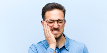 Man in denim shirt with tooth pain