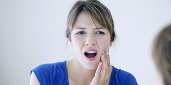 Woman in blue shirt with dental emergency