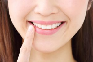 young woman smiling pointing at teeth