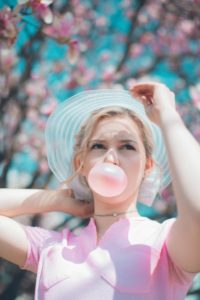 woman under cherry blossom tree chewing bubble gum