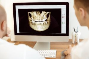 Dentist reviewing computer image for dental implants.